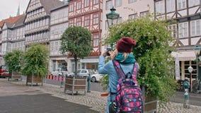 Молодой женский турист принимает фото на видимостях смартфона исторической части немецкого города ( акции видеоматериалы