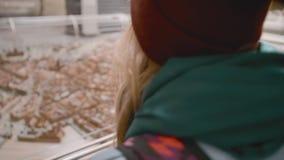 Молодой женский турист с рюкзаком на ее плечах рассматривает миниатюрную установку города с домами и видеоматериал