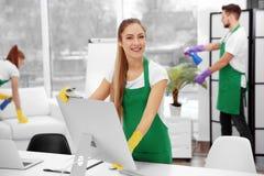 Молодой женский уборщик обтирая компьютер на офисе стоковые фото
