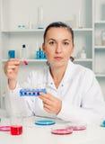 Молодой женский ученый в лаборатории, делая экспериментирует в лаборатории стоковое изображение