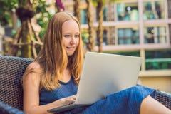 Молодой женский фрилансер сидя около бассейна с ее компьтер-книжкой в гостинице просматривая в ее smartphone Занятый на праздника стоковое изображение rf