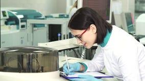 Молодой женский химик принимая примечания на современную лабораторию