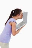 Молодой женский целуя экран компьтер-книжки Стоковое Фото
