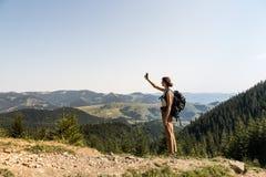 Молодой женский backpacker использует мобильный телефон для автопортрета в сельской горной области украинских прикарпатских гор Стоковая Фотография RF