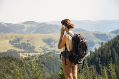 Молодой женский backpacker использует мобильный телефон для того чтобы связывать в сельской горной области украинских прикарпатск Стоковое Изображение