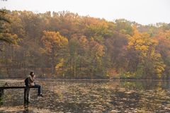 Молодой женский hiker при рюкзак сидя на речном береге и смотря красивый пейзаж бабьего лета Стоковая Фотография