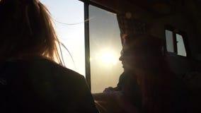 2 молодой женщины во взгляде солнца и слепимости через окно трейлера на дезертированном пляже видеоматериал