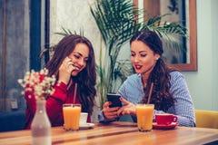 2 молодой женщины выпивая кофе и используя телефон в кафе стоковое фото