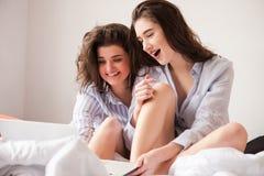 2 молодой женщины в кровати с ноутбуком стоковое фото