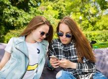 2 молодой женщины в парке смотрят телефон Стоковое Изображение RF