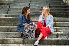 2 молодой женщины говоря и смеясь над на городских шагах Стоковое Фото