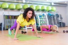 2 молодой женщины делая низкие тренировки стоя назад к со швейцарскому шарику между ими Спортсменки разрабатывая внутри стоковое фото rf