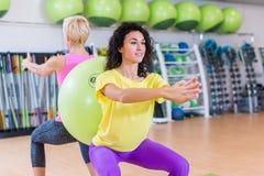2 молодой женщины делая низкие тренировки стоя назад к со швейцарскому шарику между ими Спортсменки разрабатывая внутри стоковые фото