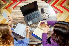 2 молодой женщины делая показатели в тетради в взгляд сверху офиса Компьтер-книжка, стекла, умный телефон на таблице Стоковое фото RF