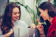 2 молодой женщины деля их новые приобретения друг с другом стоковое изображение