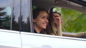 2 молодой женщины едут в автомобиле и имеют потеху Одно из их принимает фото собственной личности на камере фильма движение медле видеоматериал