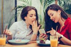 2 молодой женщины есть торты и используя телефон в кафе стоковое фото rf