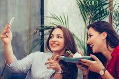 2 молодой женщины есть торты и принимая selfie со смартфоном в кафе стоковая фотография rf