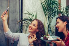 2 молодой женщины есть торты и принимая selfie со смартфоном в кафе стоковое изображение rf