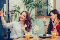 2 молодой женщины есть торты показывая В ПОРЯДКЕ жест пока принимающ selfie со смартфоном стоковая фотография