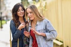 2 молодой женщины записывая сообщение голоса с умным телефоном Стоковые Изображения