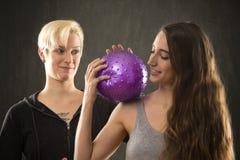 2 молодой женщины играя с фиолетовым шариком в студии Стоковое Изображение
