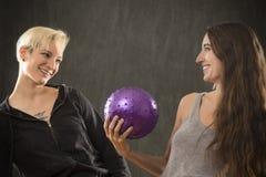 2 молодой женщины играя с фиолетовым шариком в студии Стоковое фото RF