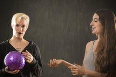 2 молодой женщины играя с фиолетовым шариком в студии Стоковое Изображение RF