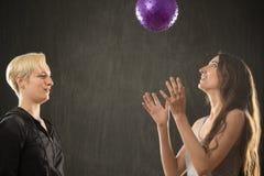 2 молодой женщины играя с фиолетовым шариком в студии Стоковые Фотографии RF