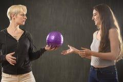 2 молодой женщины играя с фиолетовым шариком в студии Стоковые Фото
