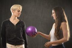 2 молодой женщины играя с фиолетовым шариком в студии Стоковая Фотография