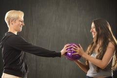 2 молодой женщины играя с фиолетовым шариком в студии Стоковое Фото