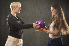 2 молодой женщины играя с фиолетовым шариком в студии Стоковые Изображения