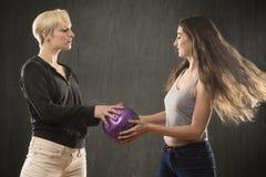 2 молодой женщины играя с фиолетовым шариком в студии Стоковая Фотография RF