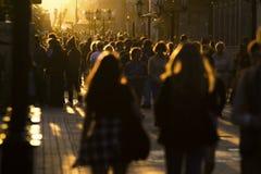2 молодой женщины идя в толпу на пешеходной улице на заходе солнца лета Стоковое Изображение RF