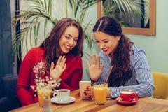 2 молодой женщины имеют видео- звонок с друзьями на смартфоне пока сидящ в кафе стоковое изображение rf