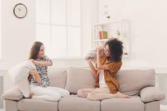 2 молодой женщины имея бой подушками на софе Стоковая Фотография RF