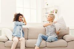 2 молодой женщины имея бой подушками на софе Стоковое Изображение RF