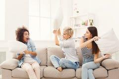 3 молодой женщины имея бой подушками на софе Стоковые Изображения