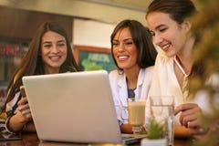 3 молодой женщины имея переговор в кафе используя верхнюю часть подола Стоковая Фотография RF