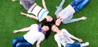 4 молодой женщины лежа на зеленой траве Стоковые Фотографии RF