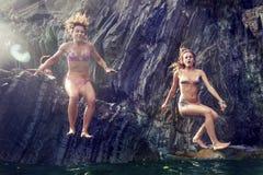 2 молодой женщины ныряя от скалы в море Стоковые Фотографии RF