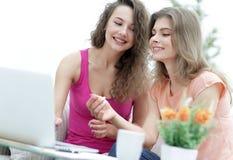 2 молодой женщины обсуждают видео при компьтер-книжка сидя на журнальном столе Стоковые Изображения