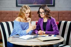 2 молодой женщины обсуждают вопросы дела смотря телефон в ресторане Стоковая Фотография