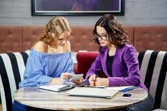 2 молодой женщины обсуждают вопросы дела смотря телефон в ресторане Стоковые Изображения RF