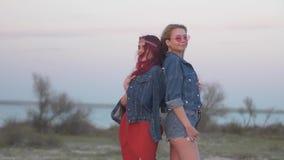2 молодой женщины одетой в куртках джинсовой ткани для того чтобы стоять спина к спине в нежных лучах захода солнца с волосами ле акции видеоматериалы