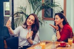 2 молодой женщины отправляя руку поцелуя и развевать онлайн во время видео- звонка с умным телефоном стоковые фотографии rf