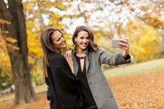 2 молодой женщины принимая selfie с мобильным телефоном в PA осени Стоковые Фото
