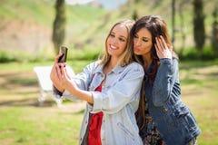 2 молодой женщины принимая selfie фотографируют в городском парке Стоковое Изображение RF