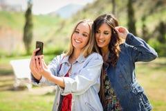 2 молодой женщины принимая selfie фотографируют в городском парке Стоковые Фотографии RF